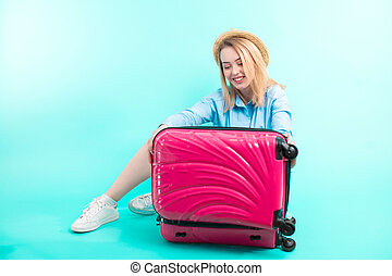 cheerful girl is going to close her baggage