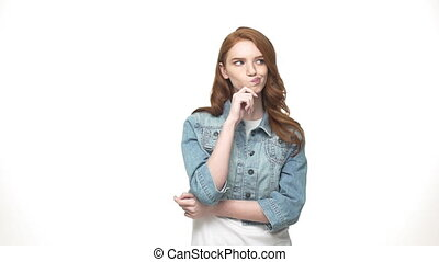 Cheerful girl is thinking on gray background. Portrait of a casual happy wondering woman in denim standing on grey background.