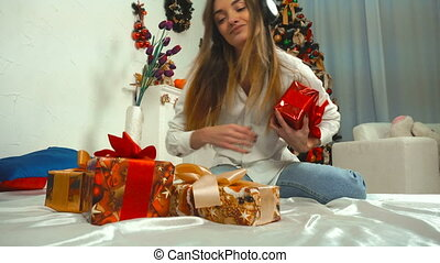 cheerful girl listens to music with headphones with a bunch of Christmas gifts