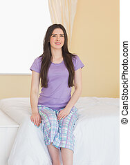 Cheerful girl looking at camera and sitting on a bed