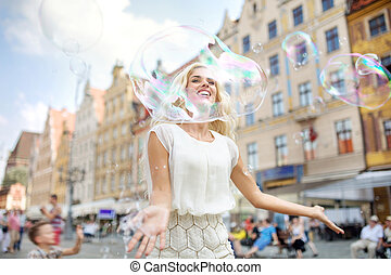 Cheerful girl looking through the huge bubble