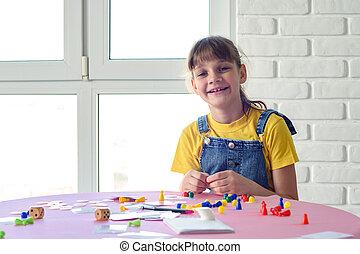 Cheerful girl plays board games at the table and looked into the frame