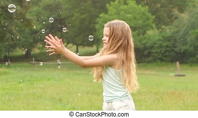 Cheerful girl plays catch soap bubbles on the meadow. Slow motion. Close up