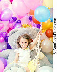 Cheerful girl posing holding bunch of balloons
