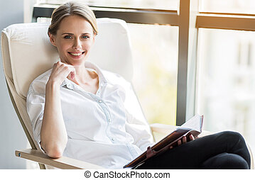 Cheerful girl reading in white chair