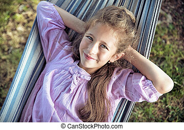 Cheerful girl resting on the hammock