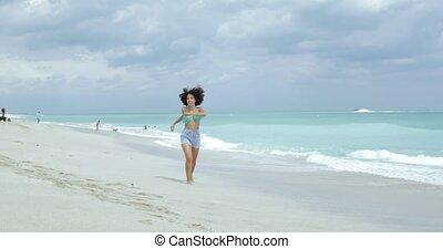 Cheerful girl running on tropical coastline