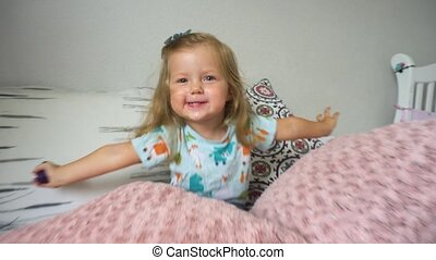 Cheerful girl sitting amidst pillows - Funny little girl...