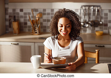 Cheerful girl sitting in the kitchen