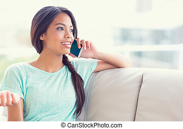 Cheerful girl sitting on sofa making a phone call at home in...