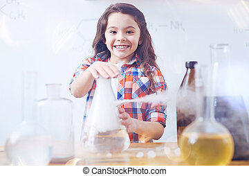 Cheerful girl smiling while touching fuming laboratory flask