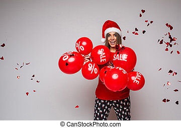 Cheerful girl with balloons and flying heart-shaped confetti and discount sign looking at camera under falling heart-shaped confetti..