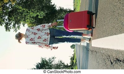 Girl with suitcase walking on road. From below shot of female smiling and pulling red suitcase while walking on asphalt road during trip through countryside. Video with Vertical Screen Orientation