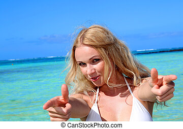 Cheerful girl with thumbs up at the beach
