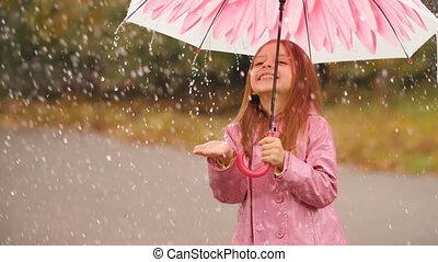Cheerful girl with umbrella under rain