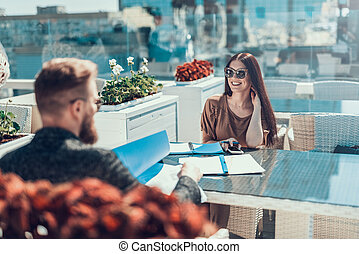 Cheerful girl working with man at table