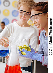 Cheerful girls mixing chemicals in a big flask