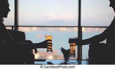 Cheerful girls talking, cheering drinking beer sitting by...