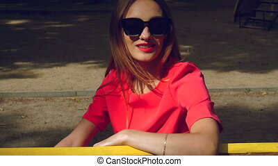 Cheerful glamour girl in red suit and black sunglasses sits on a bench at the park