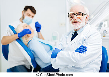 Cheerful glance of pleased stomatologist