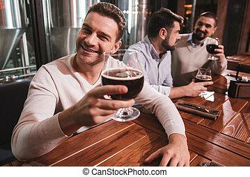 Cheerful good looking man taking pleasure in his drink