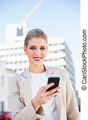 Cheerful gorgeous businesswoman sending a text message