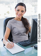 Cheerful gorgeous businesswoman taking notes