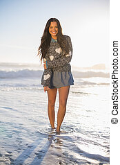 Cheerful gorgeous woman barefoot in the sea