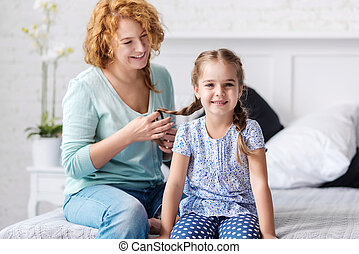 Cheerful grandmother plaiting braids to her granddaughter - ...