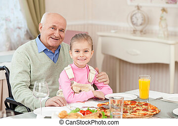 Cheerful grandparent has lunch with a child - Pretty old man...