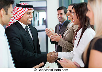cheerful group of business team welcoming arabian businessman