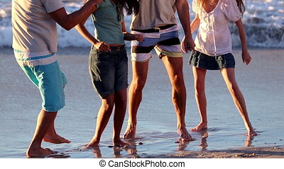 Cheerful group of friends dancing on the beach in front of the sea