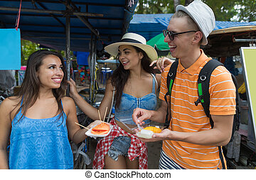 Cheerful Group Of Friends Eat Fresh Fruits Exploring Asian City And Street Cafes Tourists Happy Young People On Vacation