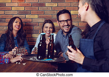 Cheerful group of friends joking and laughing with a waiter in pub.
