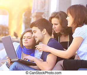 Cheerful group of students smiling and looking at a laptop.