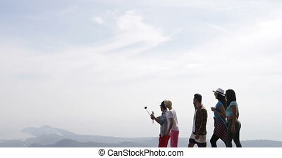 Cheerful Group Of Tourists Walk On Mountain Top Holding Action Camera Happy Men And Women Making Video Over Beautiful Landscape