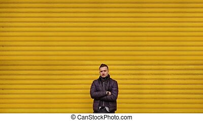 Cheerful guy in black jacket with crossed arms poses for camera near closed city store shutters computer generated imagery