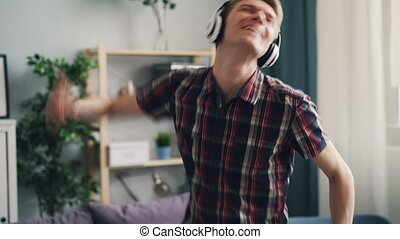 Cheerful guy is enjoying song in headphones dancing and singing listening to pop music relaxing and having fun. Millennials, gadgets and lifestyle concept.