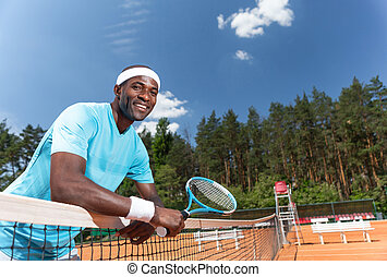 Cheerful guy is having good time during tennis game