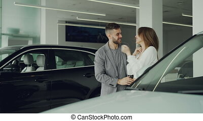 Cheerful guy is making surprise for his wife closing her eyes with his hands and leading her to beautiful new car is motor showroom, happy woman is hugging and kissing him.