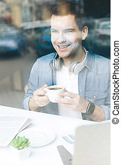 Cheerful guy is resting with hot drink