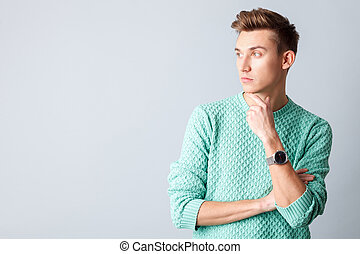 Cheerful guy is thinking about something seriously