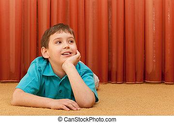 Cheerful handsome boy on the floor