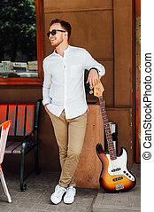 cheerful handsome guy stands near a guitar