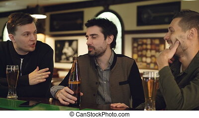 Cheerful handsome guys are having conversation in bar over...