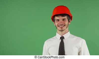 Cheerful handsome male engineer wearing hardhat winking to the camera