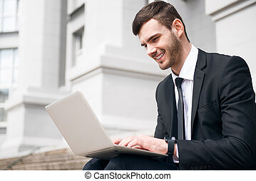 Cheerful handsome man using laptop