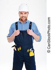 Cheerful handsome young builder in helmet standing and smiling