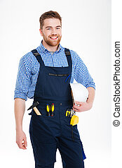 Cheerful handsome young builder in overall standing and...