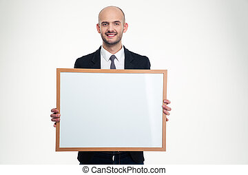 Cheerful handsome young businessman holding blank board